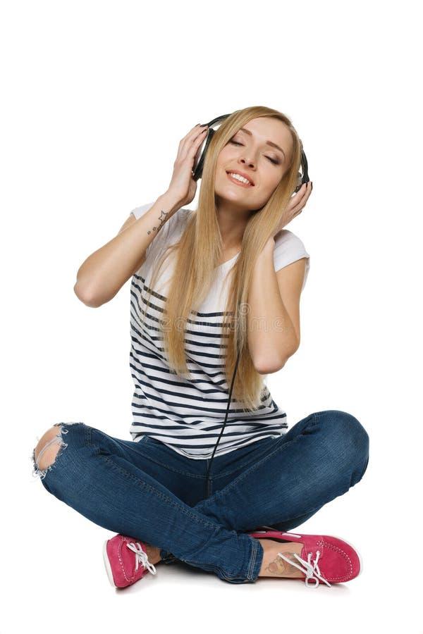 Fêmea que senta-se no assoalho que aprecia a música nos auscultadores com olhos fechados fotografia de stock