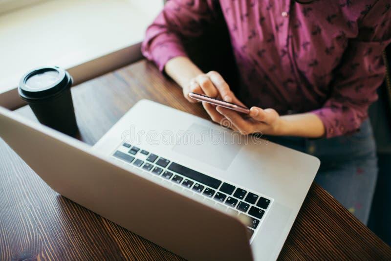 Fêmea que usa o telefone e o portátil em um café imagem de stock royalty free