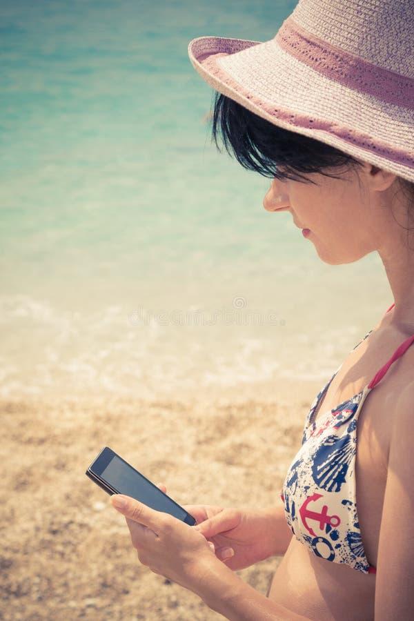 Fêmea que usa o telefone esperto na praia fotografia de stock royalty free