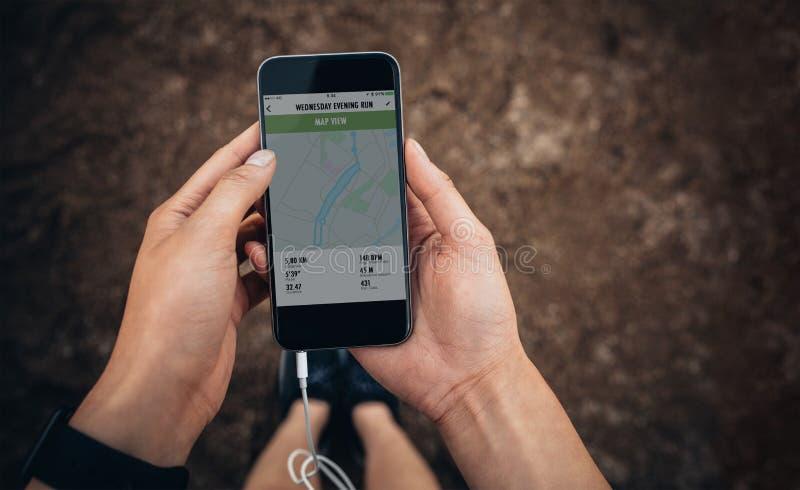 Fêmea que verifica o sumário de sua corrida no telefone celular imagem de stock royalty free