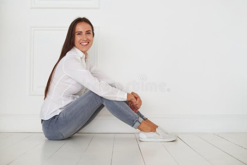 A fêmea relaxado e ensolarada está sentando-se no assoalho fotografia de stock