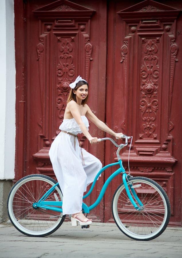 A fêmea senta-se na bicicleta contra na porta vermelha velha do fundo fotos de stock royalty free