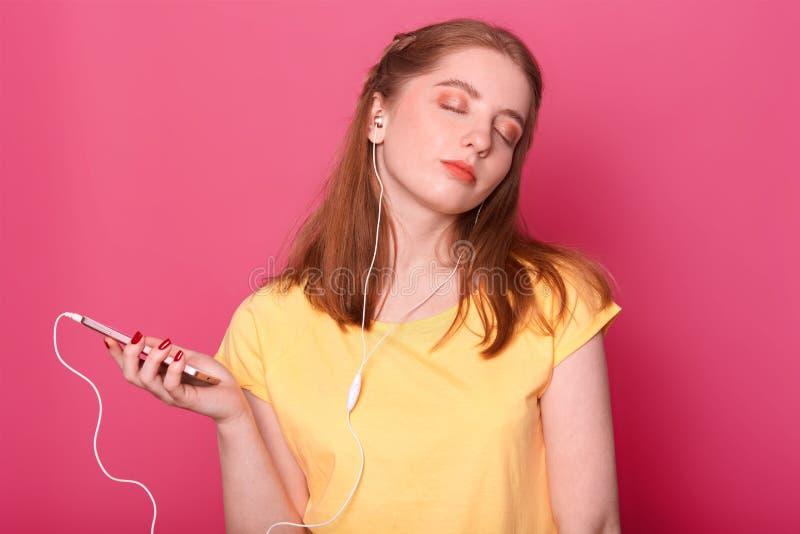 A fêmea sonhadora com expressão pensativa e os olhos closeed, têm fones de ouvido modernos, escutam a música, passam o tempo de l foto de stock