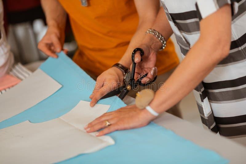 A fêmea superior costura as mãos que corta um teste padrão foto de stock