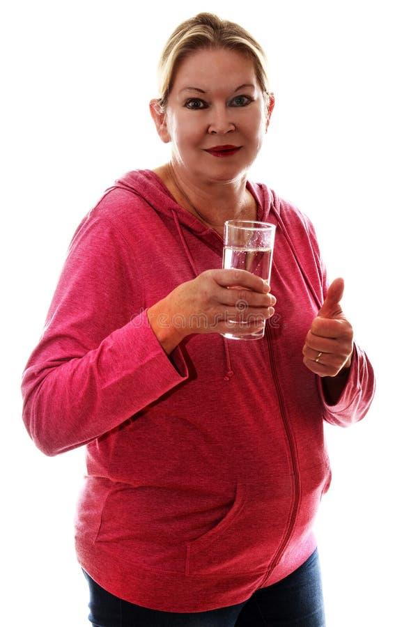 Fêmea superior loura em uma camiseta cor-de-rosa que bebe um sparklin de vidro fotos de stock