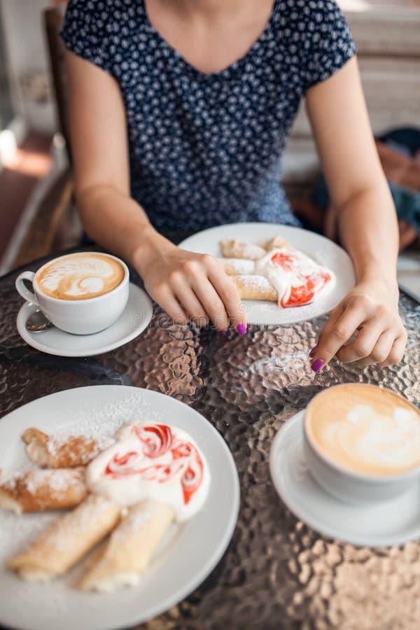 A fêmea tem um almoço com café e panquecas, imagens de stock royalty free