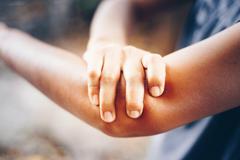 Fêmea tendo a dor no braço ferido foto de stock royalty free