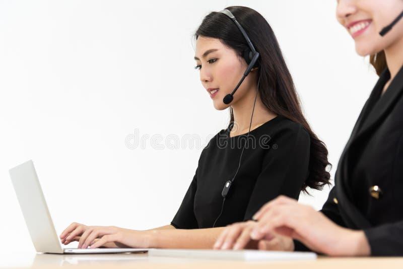 Fêmeas asiáticas no funcionamento preto da camisa no portátil e nos auriculares foto de stock royalty free