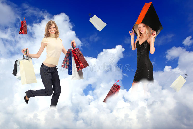 Fêmeas da compra com os sacos nas nuvens brancas imagem de stock