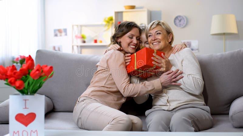 Fêmeas e menina que abraçam, caixa de presente da terra arrendada da avó, felicitações do aniversário imagens de stock royalty free