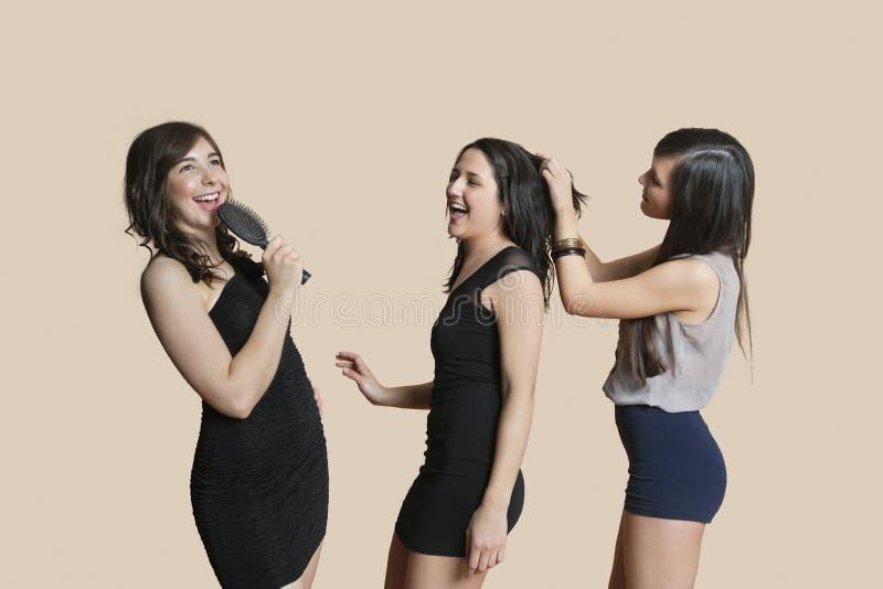 Fêmeas novas alegres que apreciam junto sobre o fundo colorido imagem de stock