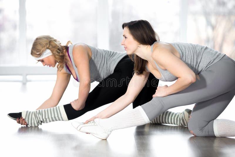 Fêmeas novas desportivas que fazem esticando exercícios da ginástica aeróbica fotos de stock