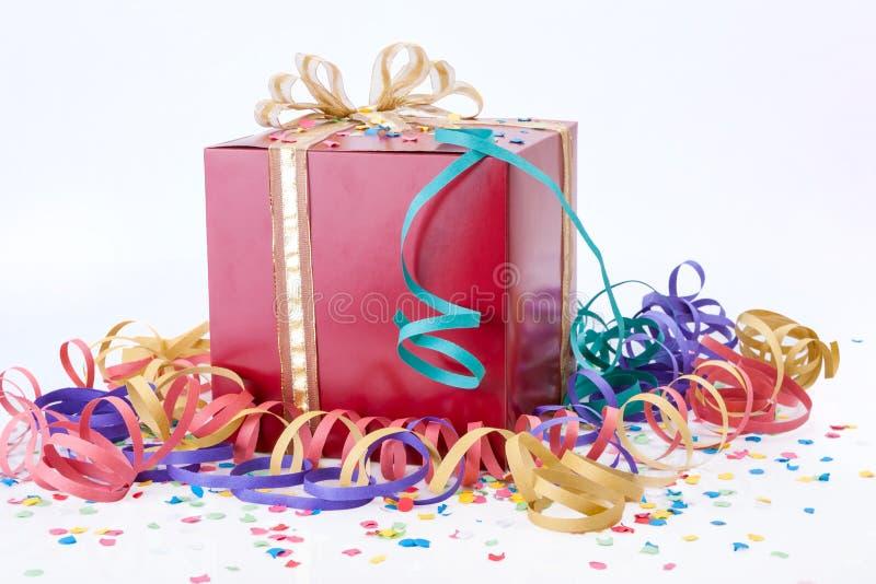 Fête d'anniversaire avec un boîte-cadeau rouge, un arc d'or photos libres de droits