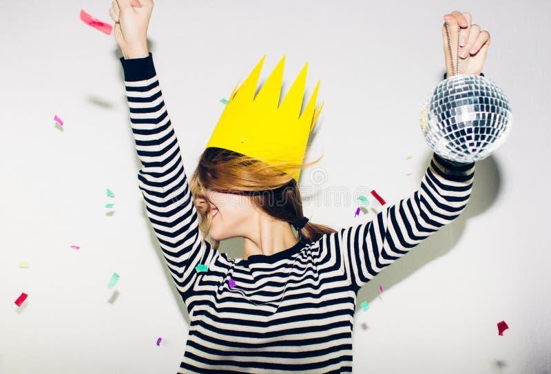 Fête d'anniversaire, carnaval de nouvelle année La jeune femme de sourire sur le fond blanc célébrant l'événement brightful, port image libre de droits
