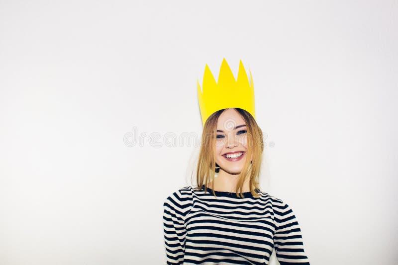 Fête d'anniversaire, carnaval de nouvelle année La jeune femme de sourire sur le fond blanc célébrant l'événement brightful, port images stock