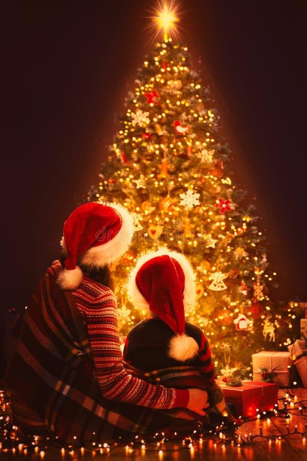 Fête de Noël Eclairage de Noël Arbre, mère et enfant en chapeau de Noël rouge, Nuit du Nouvel An images stock