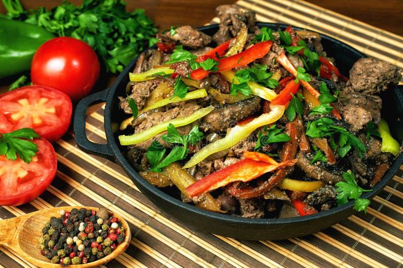 Fígado de frango frito em uma bandeja do ferro fundido com os vegetais na tabela de madeira fotografia de stock