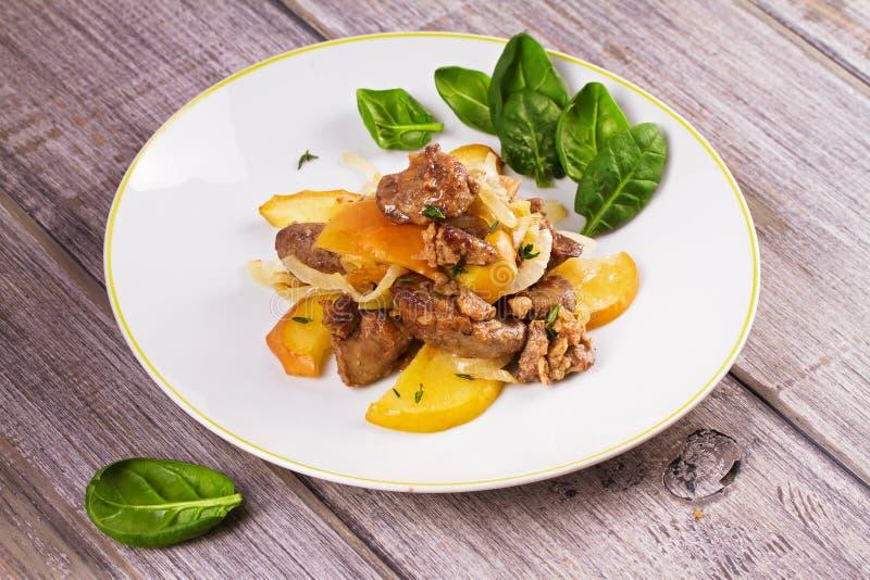 Fígado de galinha com maçã, espinafres e cebola fotos de stock royalty free