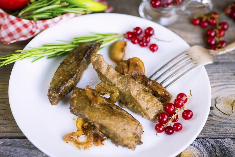 Fígado fritado com cebolas e vegetais foto de stock