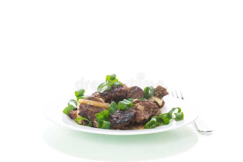 Fígado fritado com cebolas em uma placa em um branco fotografia de stock royalty free