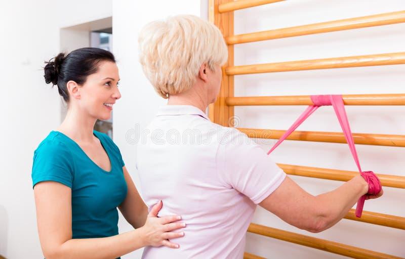 Físico mulher idosa de ajuda durante o exercício com faixa a do poder imagens de stock royalty free