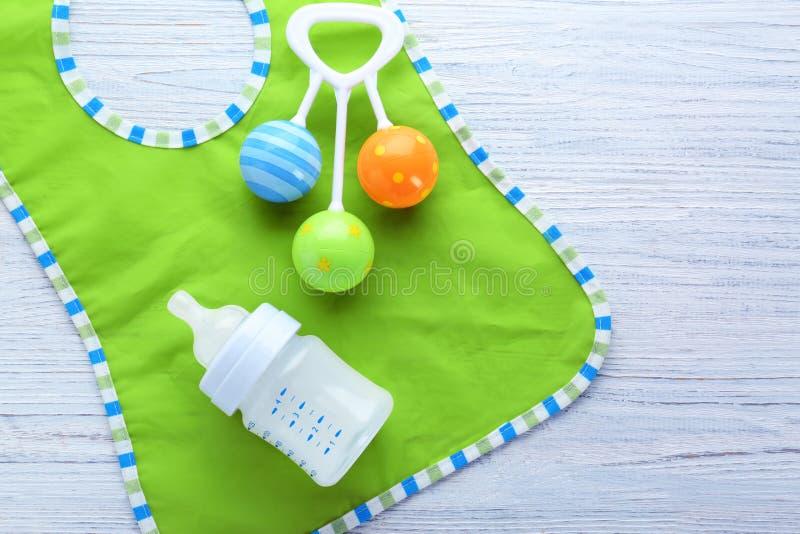 Fórmula, babador e chocalho do leite do bebê no fundo fotos de stock