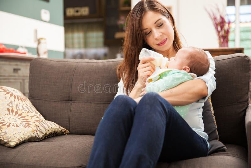 Fórmula de alimentación de la mujer a su bebé foto de archivo libre de regalías