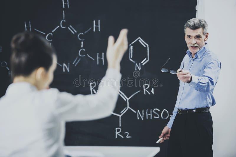 Fórmula de la química de profesor Ask Student About fotografía de archivo