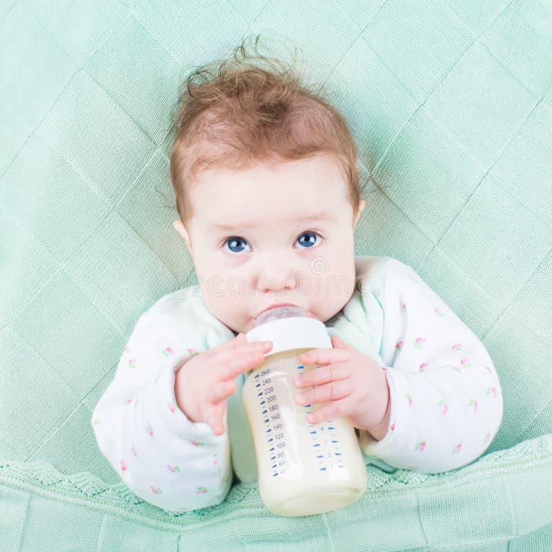 Fórmula pequena bonito do leite bebendo do bebê fora da garrafa imagem de stock