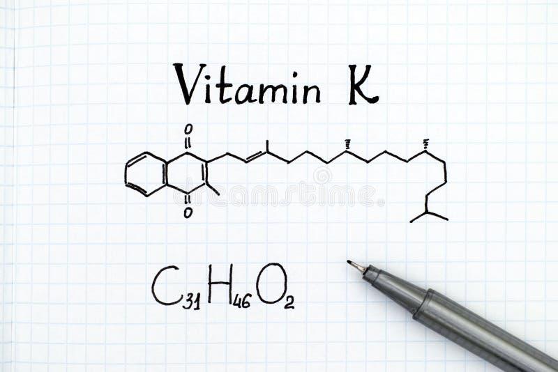 Fórmula química de la vitamina K con la pluma fotos de archivo libres de regalías