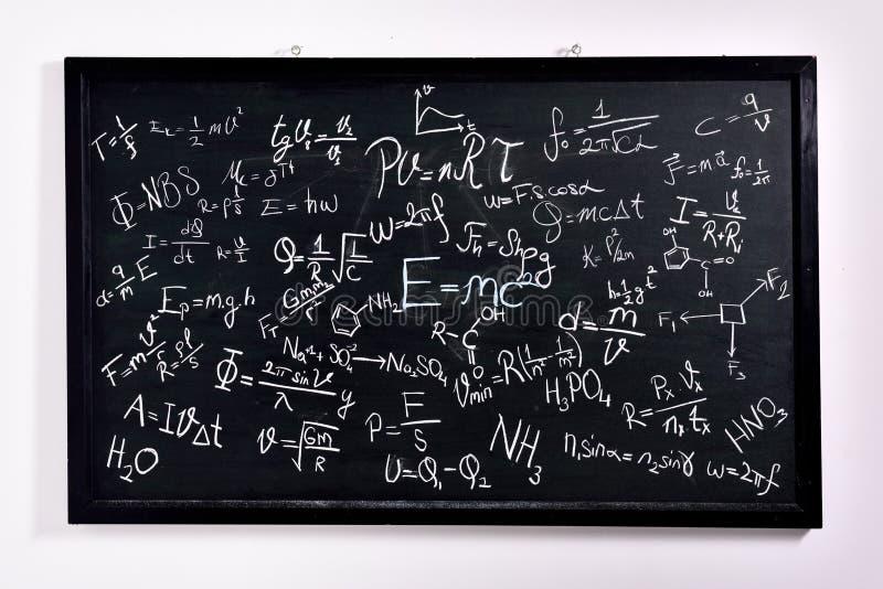 Fórmulas e fenômenos físicos na placa de escola imagem de stock