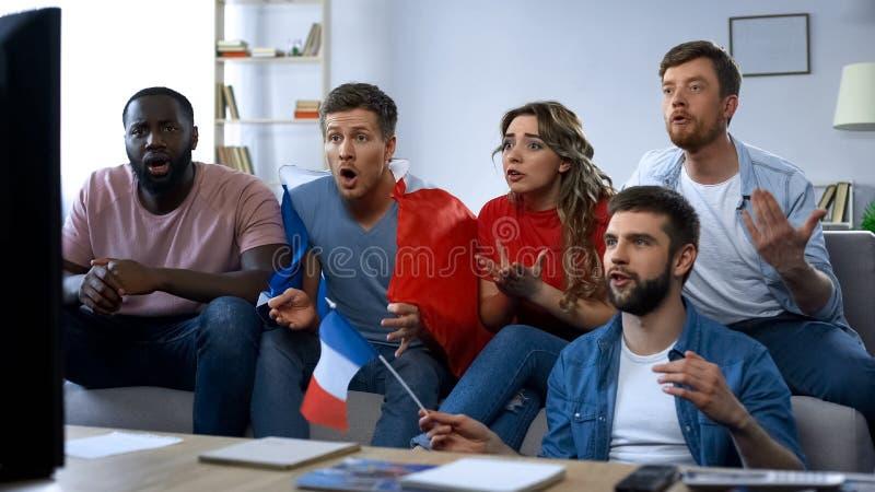 Fósforo de observação dos amigos franceses na tevê em casa, apoiando a equipe de futebol favorita imagens de stock