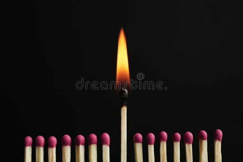 F?sforo de queimadura entre outros Conceito da diferen?a e da unicidade foto de stock