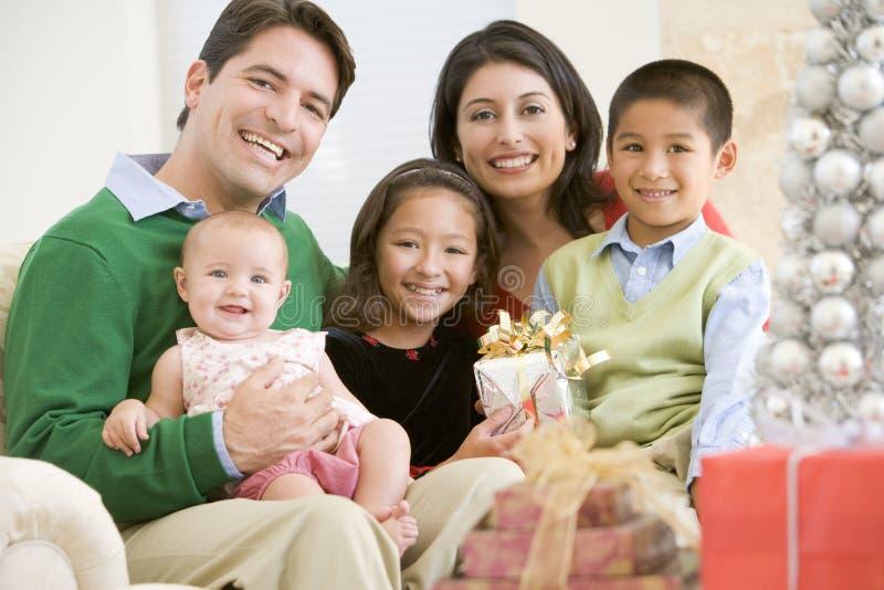 född familj som rymmer den nya prese sittande sofaen royaltyfria foton