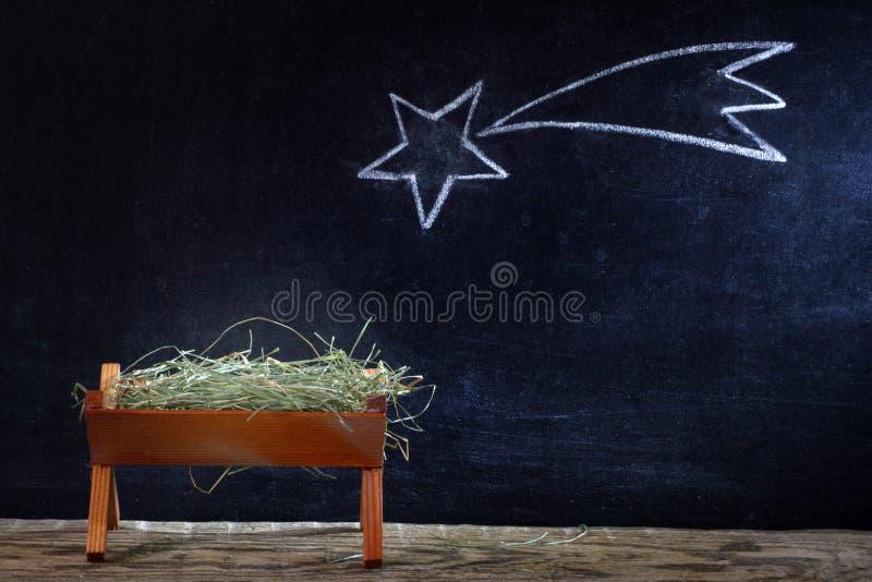 Födelse av Jesus med krubban och stjärnan på svart tavla arkivfoto