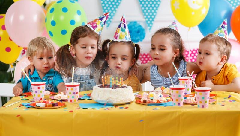 Födelsedag för barn` s lyckliga ungar med kakan arkivbild