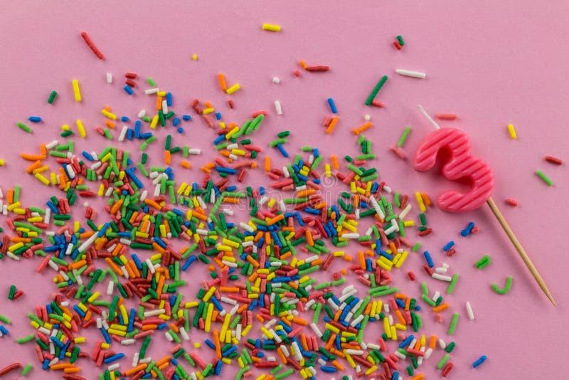 Födelsedagbakgrund med denfärgade kakan som överträffar stänk och nummer 3 födelsedag stearinljus på rosa bakgrund med kopierings royaltyfria foton