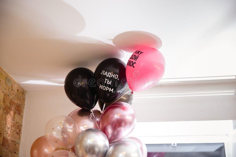 Födelsedagballonger under ett tak med ok ryssord, är du fint, och jag ser ett grått hår royaltyfria foton