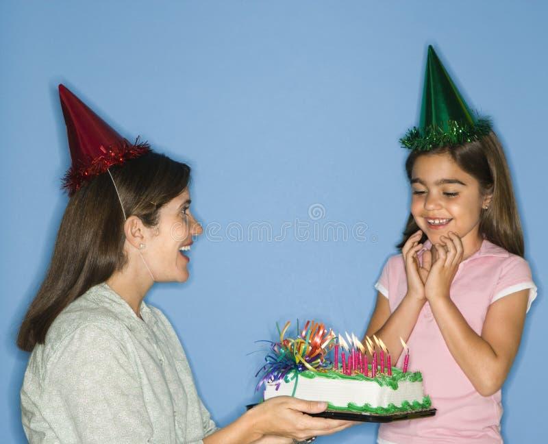 födelsedagcake som får flickan royaltyfri foto