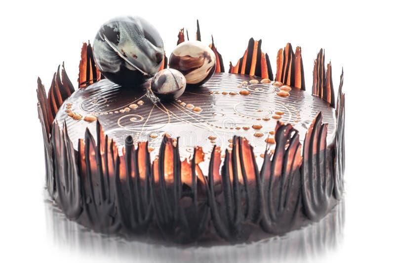 Födelsedagchokladkakan med chokladbollgarnering, stycke av den kräm- kakan, bakelser, fotografi för shoppar, den söta efterrätten royaltyfria foton