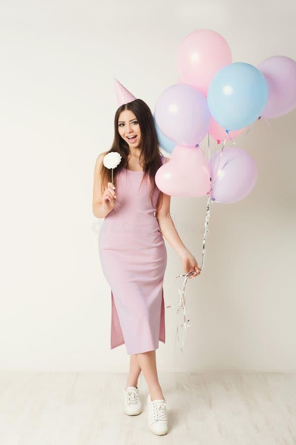 Födelsedagflicka i ballonger för partihattinnehav royaltyfri bild