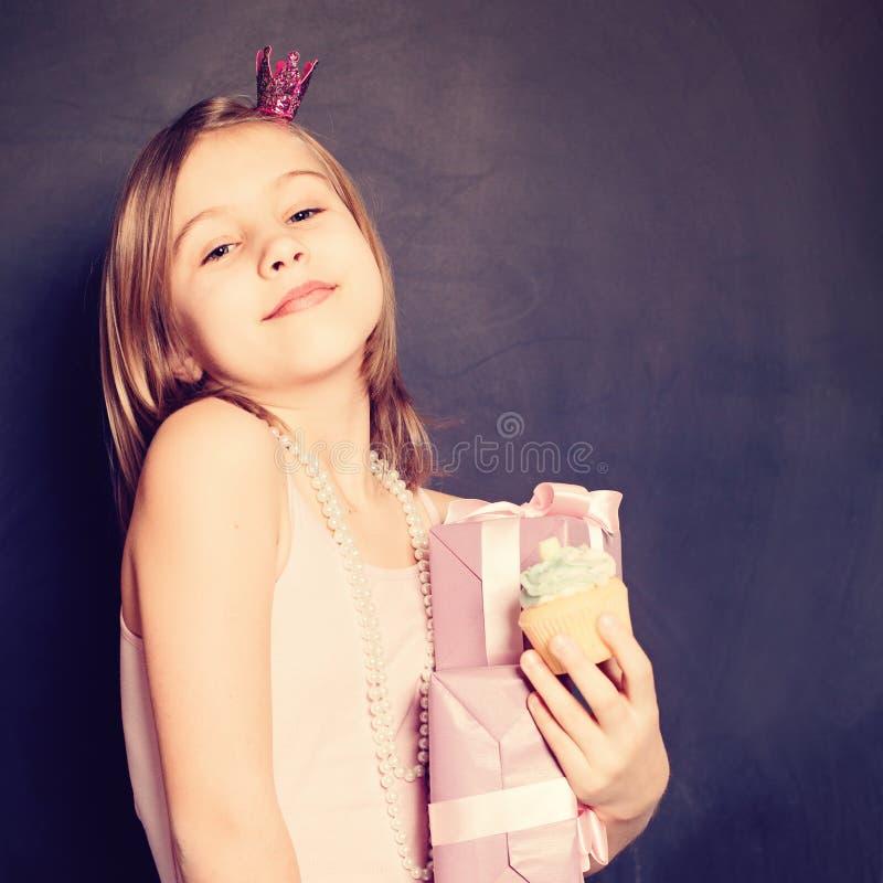 Födelsedagflicka med den rosa den gåvaasken och kakan på bakgrund arkivfoto