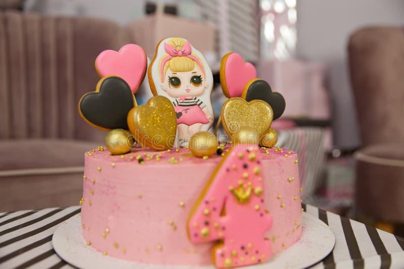 Födelsedagkaka för 4 år som dekoreras med pepparkakahjärtor med isläggning och numret fyra blek maräng - rosa royaltyfri fotografi