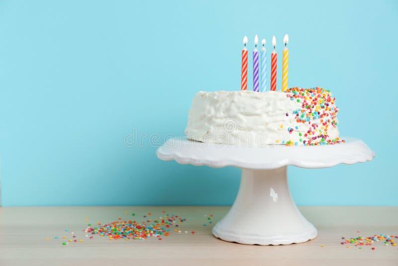 Födelsedagkaka med stearinljus på tabellen arkivfoto