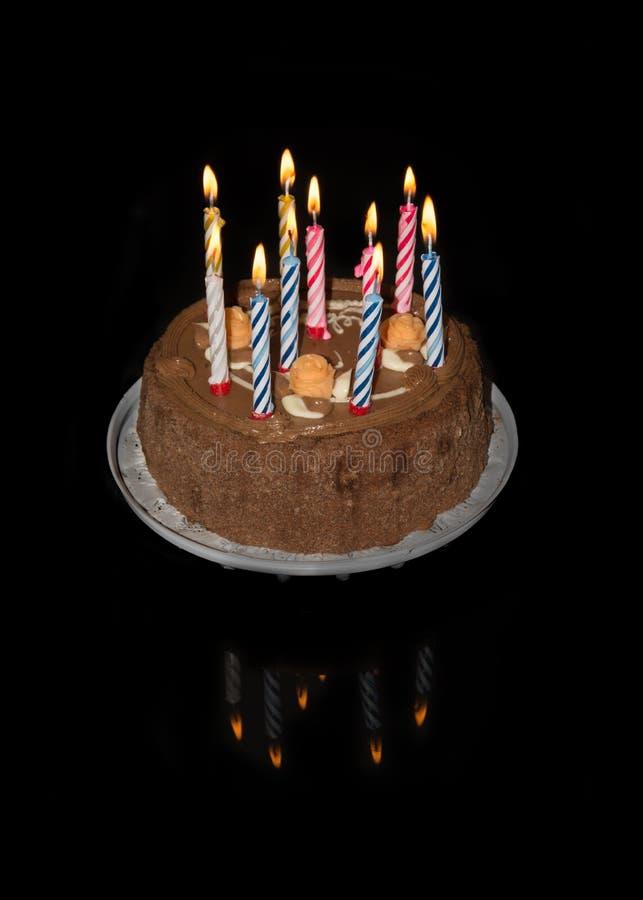 Födelsedagkaka på svart bakgrund med tio färgrika tända stearinljus arkivbilder