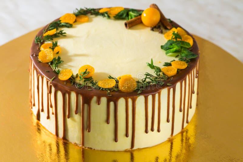 Födelsedagkakan med kräm- choklad dryper på en guld- bakgrund arkivfoton
