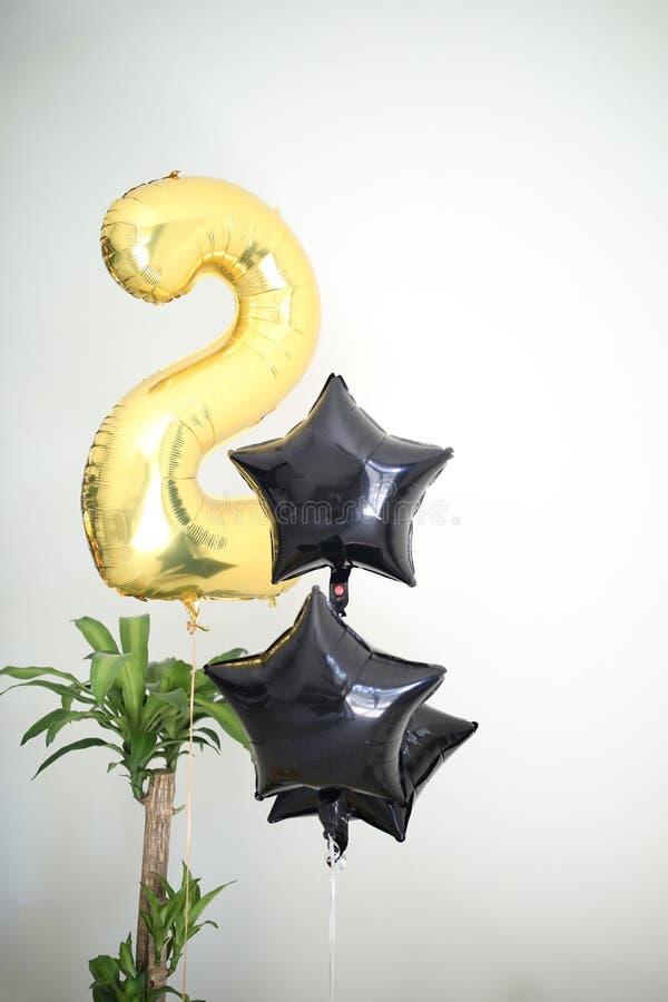 Födelsedagluftballons ställde in, guld- nummer två och svarta formade stjärnor arkivfoto