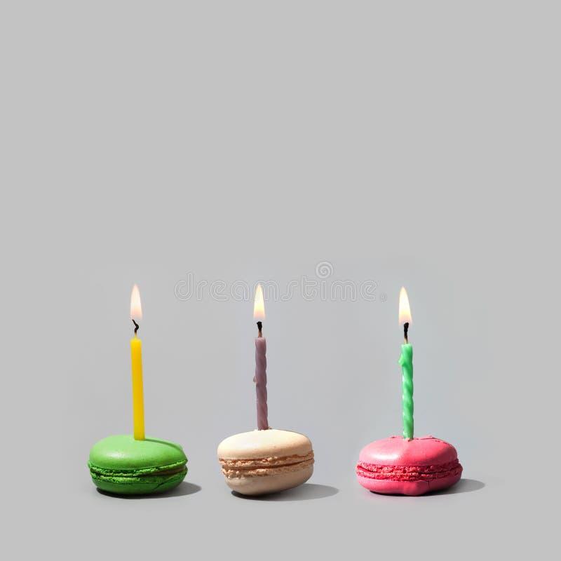Födelsedagmakron med mångfärgade bränningstearinljus Semestra färgrik fransk söt läckerhet för inbjudanmallen på grå färger royaltyfria foton