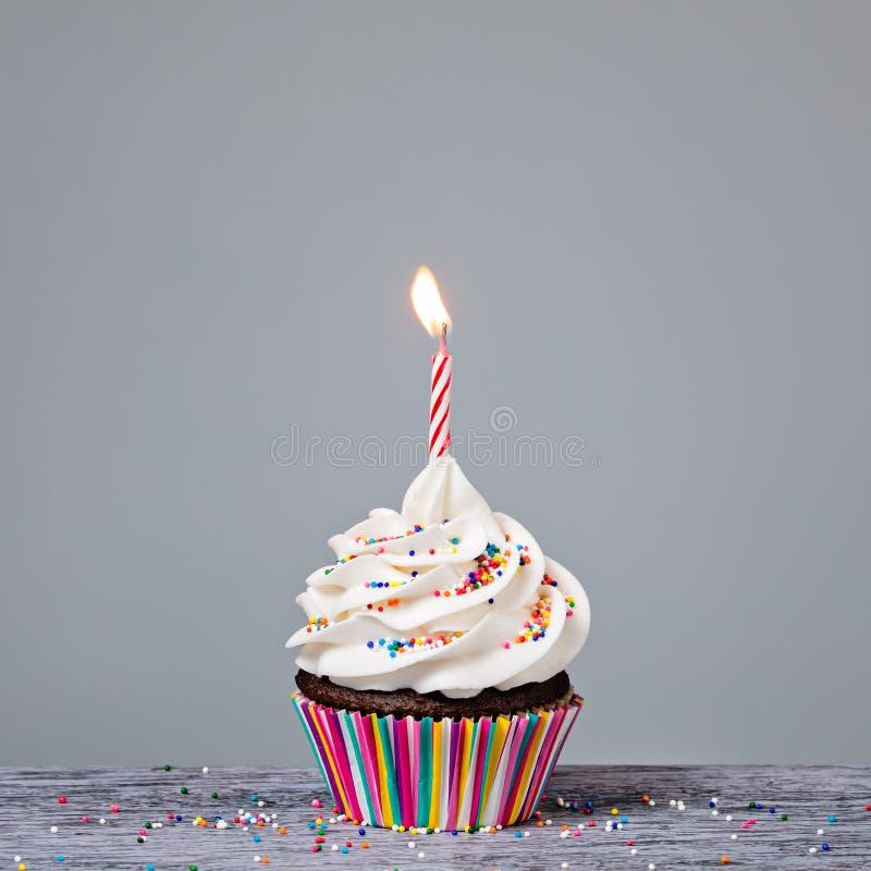 Födelsedagmuffin med den röda stearinljuset royaltyfria bilder