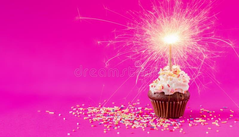 Födelsedagmuffin med ett tomtebloss på rosa bakgrund arkivbild
